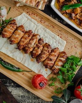 Krajowy grill kebab z mięsem w lawaszu z natką pietruszki i grillowanym pomidorem.