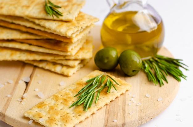 Krakersy bezglutenowe z rozmarynem, oliwkami i oliwą z oliwek na desce.