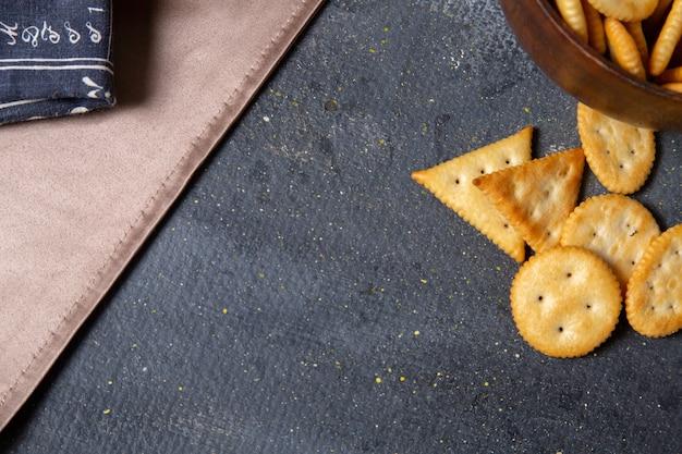 Krakersy i chipsy z bliska z góry na ciemnym tle chrupiąca przekąska z krakersem solnym