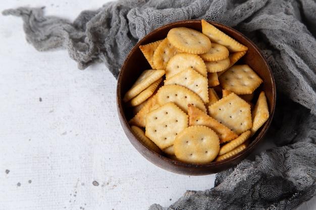 Krakersy i chipsy z widokiem z góry na brązowym talerzu na jasnym tle
