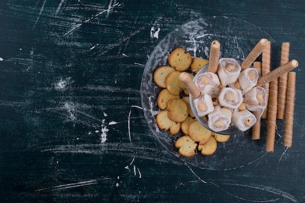 Krakersy i gofry z tureckim lokum w szklanym talerzu, widok z góry