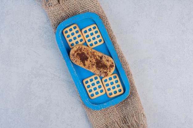 Krakersy i mały tort na niebieskim talerzu na marmurowym stole.