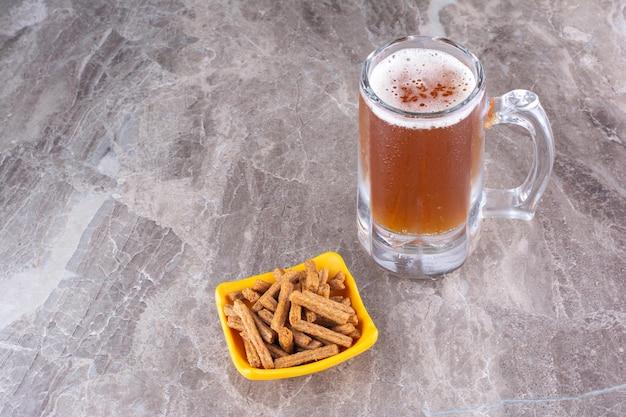 Krakersy i szklankę zimnego piwa na marmurowej powierzchni. zdjęcie wysokiej jakości