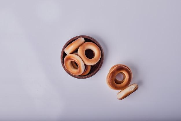 Krakersy lub bułeczki z ciasta w drewnianym kubku, widok z góry.
