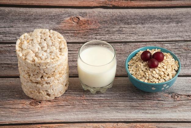 Krakersy owsiane, ziarna z jagodami i filiżankę mleka na stole
