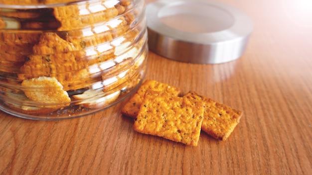 Krakersy pszenne w szklanym słoju na drewnianym stole. pojęcie kuchni i jedzenia