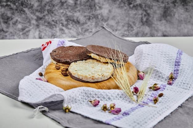 Krakersy ryżowo-czekoladowe na drewnianym talerzu z obrusem.