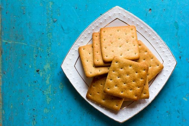 Krakersy w białym ceramicznym kwadratowym spodku na starym niebieskim drewnie