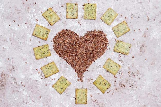 Krakersy w kształcie serca z nasion lnu z oliwą z oliwek, nasion lnu i zieleni, widok z góry