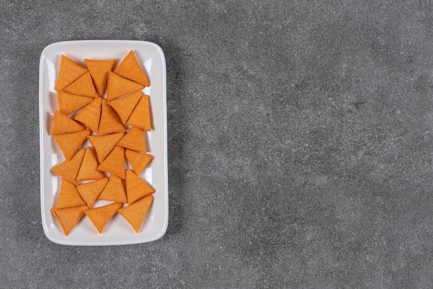 Krakersy w kształcie trójkąta na białym talerzu.