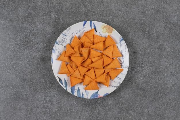Krakersy w kształcie trójkąta na kolorowym talerzu.