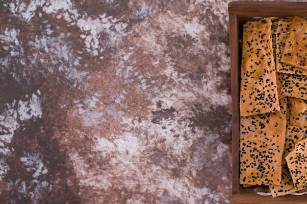 Krakersy z czarnuszką na drewnianej tacy po prawej stronie.