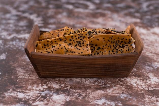 Krakersy z czarnuszką na drewnianej tacy, widok pod kątem.