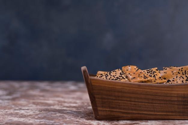 Krakersy z czarnuszką na drewnianej tacy.
