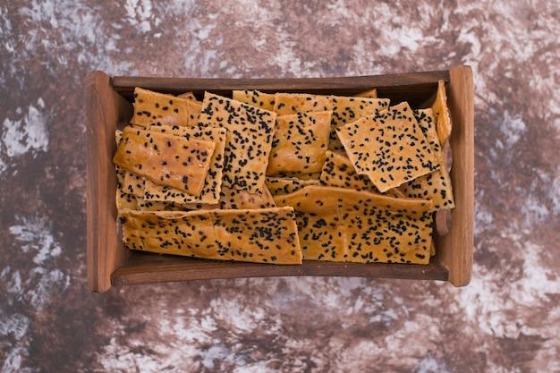 Krakersy z czarnuszką na środku na drewnianej tacy