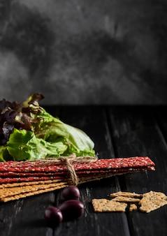 Krakersy z mąki buraczanej i żytniej z warzywami do robienia przekąsek na czarnej ścianie. wegetarianizm i zdrowe odżywianie