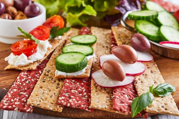 Krakersy z mąki buraczanej i żytniej z warzywami do robienia przekąsek na drewnianej ścianie. wegetarianizm i zdrowe odżywianie