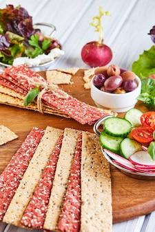 Krakersy z mąki buraczanej i żytniej z warzywami do robienia przekąsek na drewnianym stole. wegetarianizm i zdrowe odżywianie