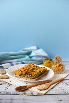 Krakersy z pastą z ciecierzycy na niebieskim tle. kanapki z hummusem. wielkopostne jedzenie wegetariańskie