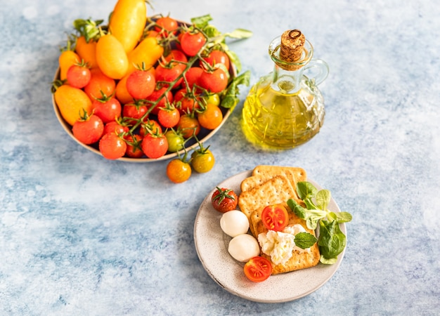 Krakersy z pomidorkami koktajlowymi, zieloną sałatą i mozzarellą, niebieskie tło betonu.