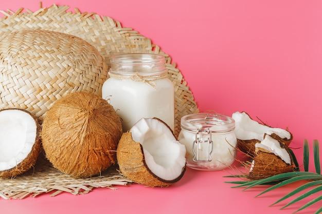 Krakingowe kokosowe i kokosowe mleko w szkle na jaskrawym różowym tle