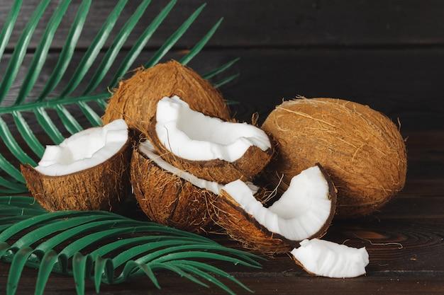 Krakingowi kokosów kawałki na ciemnym drewnianym tle