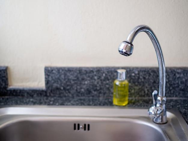 Kran i butelka płynu do mycia naczyń na zlewie