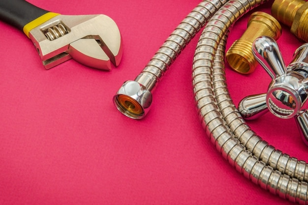 Kran, narzędzie i wąż do materiałów sanitarnych na fioletowej przestrzeni są używane do wymiany pod prysznicem