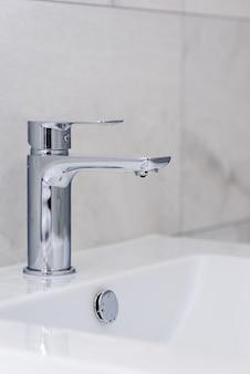 Kran z kroplą wody i zlew na ścianie z szarych płytek. wnętrze łazienki po remoncie. oszczędność wody.