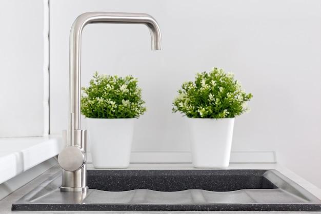 Kran z umywalką i roślinami ozdobnymi w kuchni.