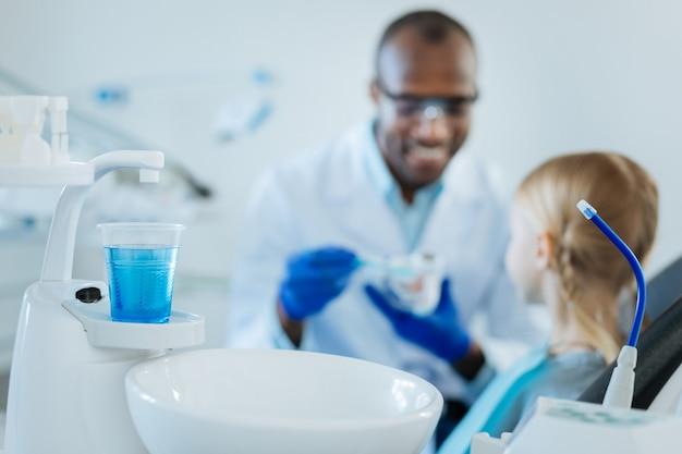 Kranik z wodą i miskę do plucia stojąc w gabinecie stomatologa podczas rozmowy o pielęgnacji zębów