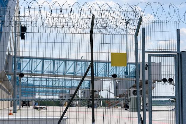 Kratka ogrodzeniowa lotniska na tle mostów pasażerskich do wsiadania pasażerów. miejsce do testu na talerzu.