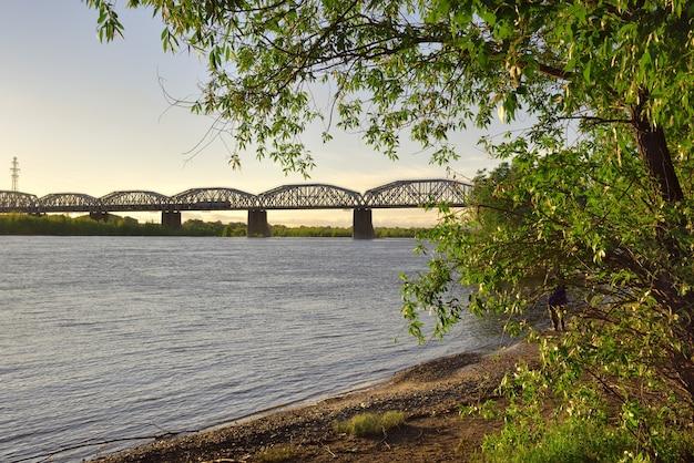 Kratownice mostowe na wysokich podporach brzeg wielkiej syberyjskiej rzeki drzewa piasek błękitne niebo