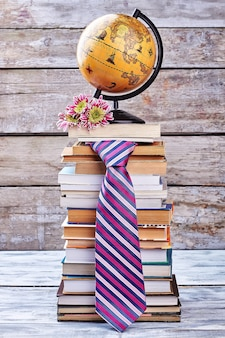 Krawat, kwiaty i kula ziemska. stos książek na półce.