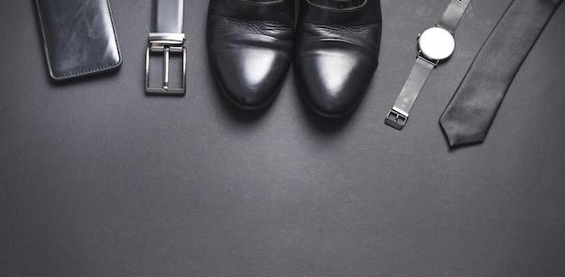 Krawat, pasek, portfel, zegarek, buty na czarnym tle. akcesoria męskie