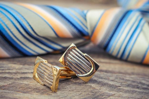Krawat, spinki do mankietów i zegarki na tle starego drewna