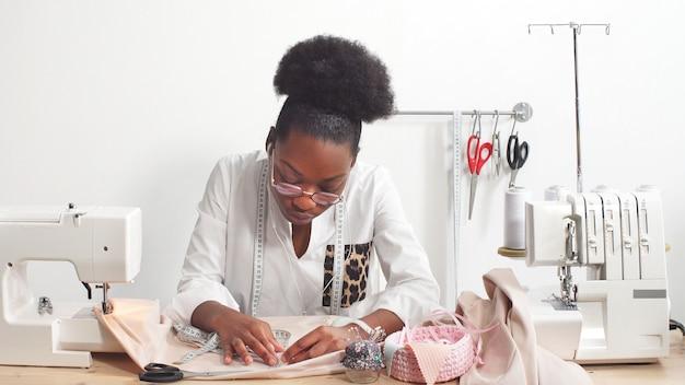 Krawcowa afroamerykańska kobieta, projektantka mody słuchająca muzyki przez słuchawki podczas pracy na tkaninie w pracowni studio