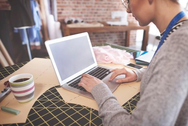 Krawcowa badająca nowe trendy za pomocą laptopa