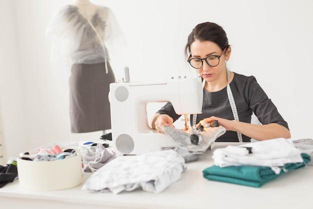 Krawcowa, krawiec i koncepcja kreatywna - portret projektantki mody z maszyną do szycia na białym tle