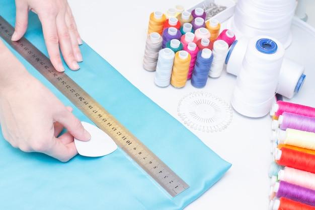 Krawcowa okrąża wzór na zbliżeniu materiału. komplet elementów do robótek ręcznych: nici, igły, szpilki, nożyczki, taśma miernicza itp.