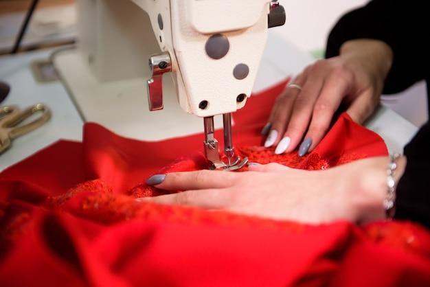 Krawcowa pracuje do szycia ubrań w maszynie do szycia, zbliżenie rąk.