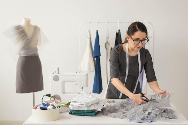 Krawcowa, projektantka mody i koncepcja krawiecka - młoda projektantka tnie lekkie tkaniny