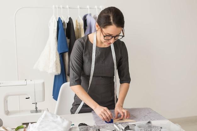 Krawcowa, projektantka mody i koncepcja krawiecka - piękna młoda stylistka w miejscu pracy w pobliżu regału