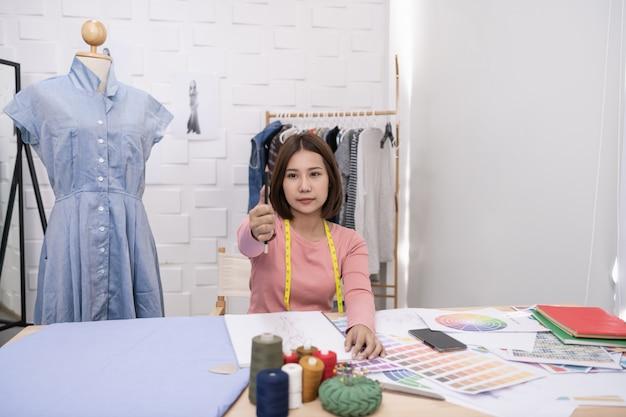 Krawcowa projektuje suknię wieczorową w pokoju. krawiec pracuje najlepiej.