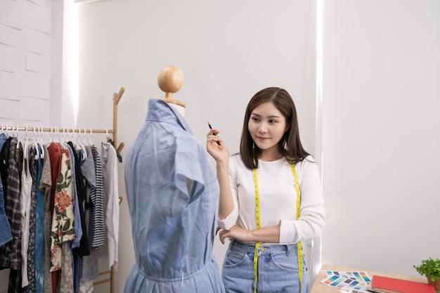 Krawcowa projektuje suknię wieczorową w pokoju.
