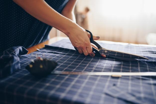 Krawcowa przecina tkaninę na sukienkę.