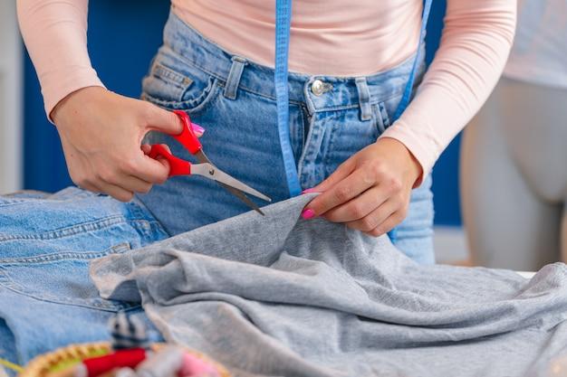 Krawcowa ręce wycinając kawałek materiału nożyczkami