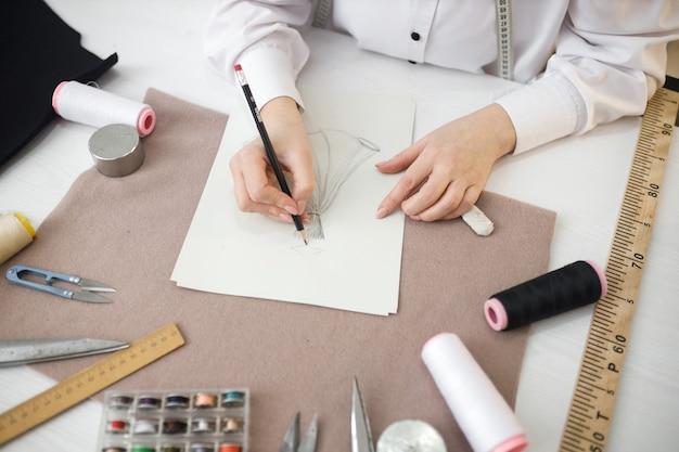 Krawcowa szkicuje przyszłą sukienkę do szycia