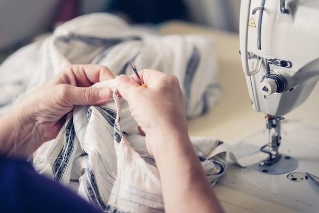 Krawcowa szyje na maszynie do szycia. miejsce pracy krawcowej. krawcowa wycina szczegóły sukni na liniach szkicu.