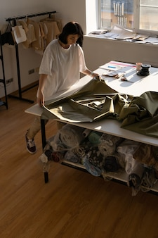 Krawcowa szyje nową kolekcję w warsztacie z modnej tkaniny na stole roboczym w atelier